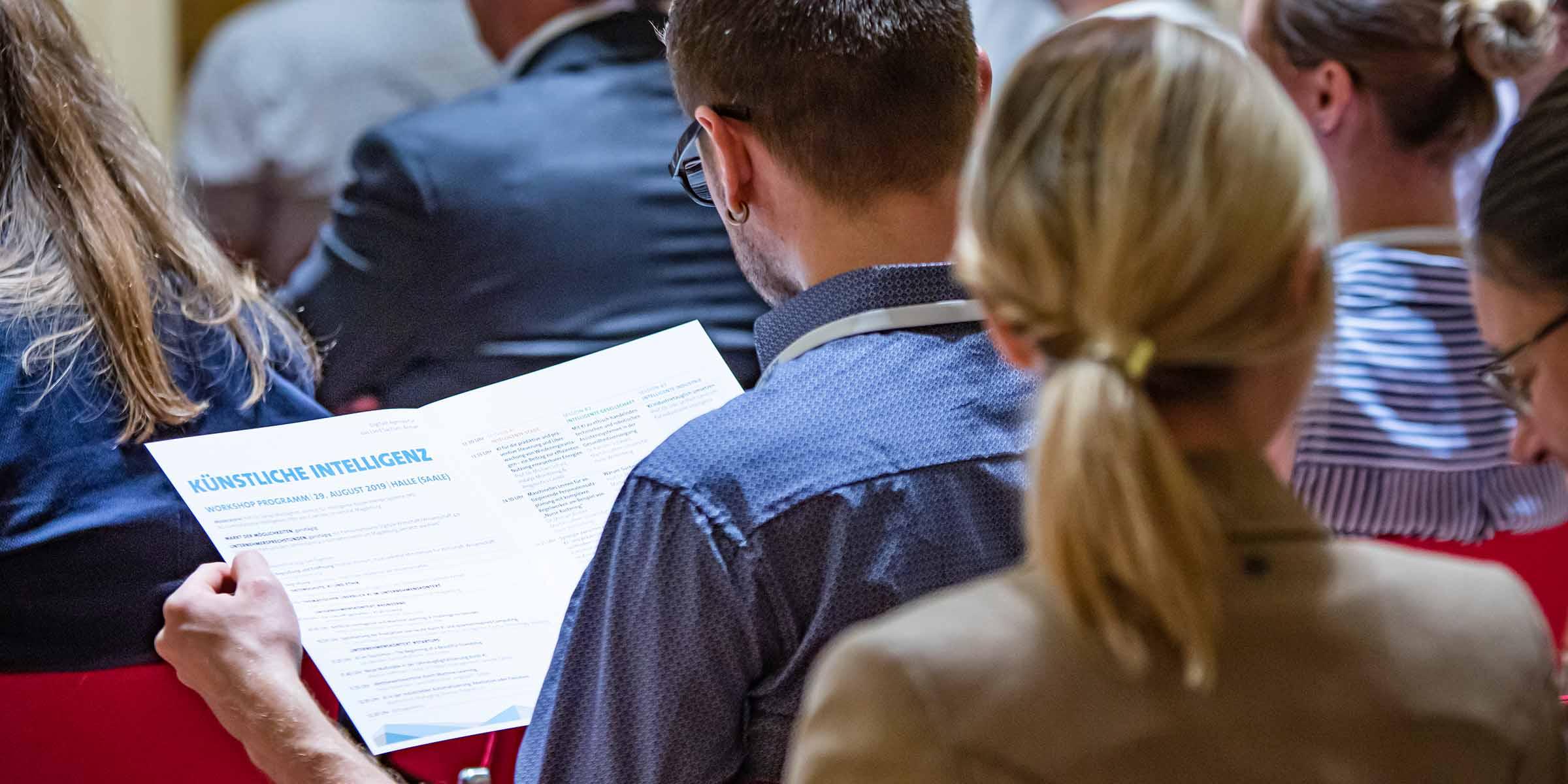 Ein Mann liest die Broschüre über künstliche Intelligenz auf der Digitalen Agenda für das Land Sachsen-Anhalt