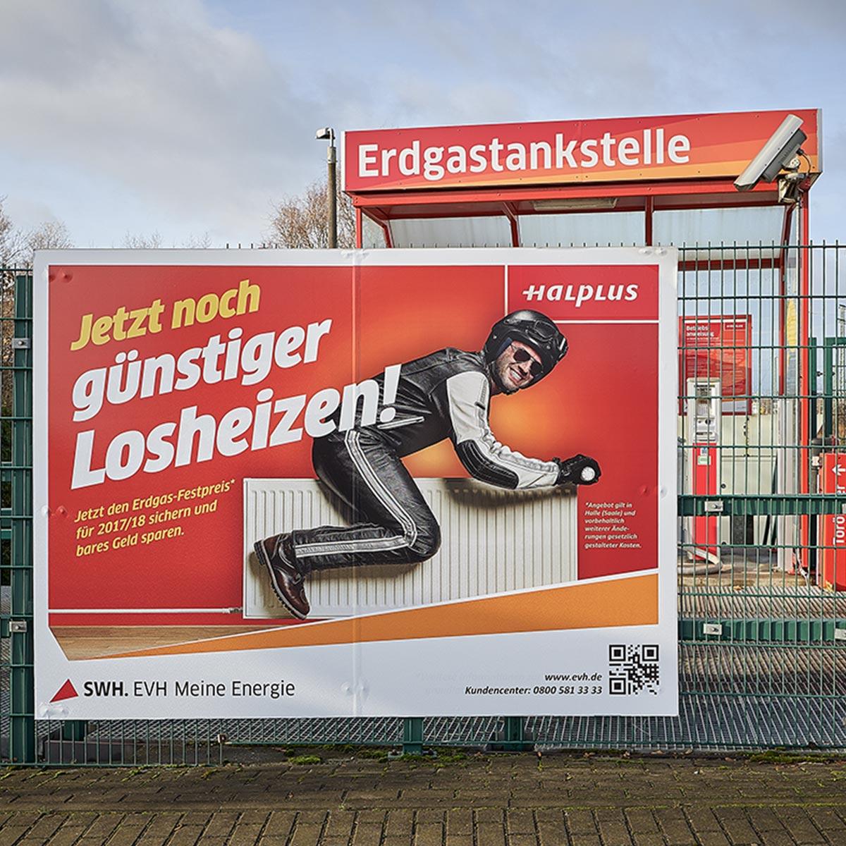 """Plakat an der Erdgastankstelle in der Freiimfelder Straße für EVH Halle: Kampagne """"Jetzt noch günstiger Losheizen!"""" Werbemotiv: Mann fährt Motorrad auf Heizungskörper"""